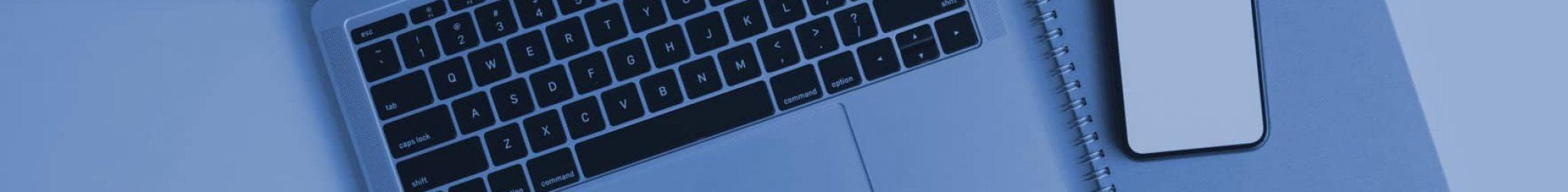 Macbook mit Smartphone und Kaffeetasse daneben.